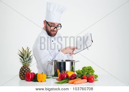 Portrait of a handsome male chef cook in glasses holding receipe book and looking at camera isolated on a white background