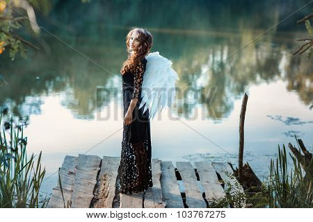 Girl With Angel Wings Standing On The Pier And Smiling.