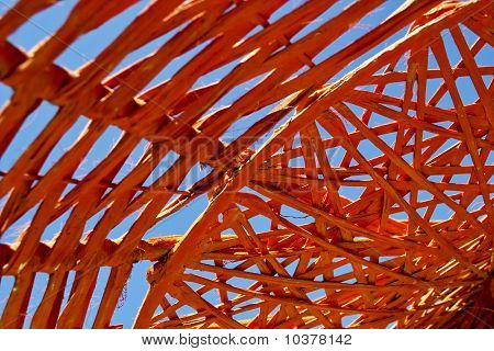 Bright orange thatched parasol under a blue sky poster