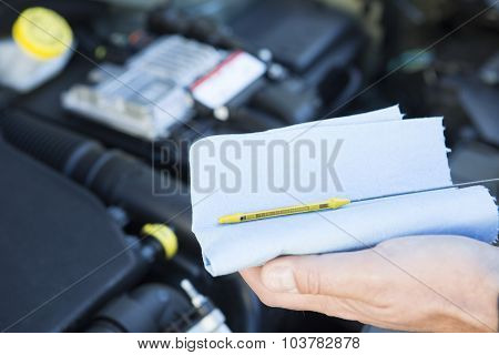 Close-up Of Man Checking Car Engine Oil Level On Dipstick