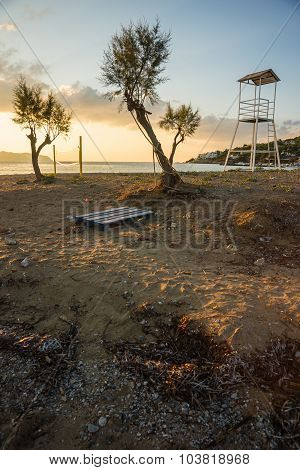 Volleyball tower net and three trees on sandy beach near the town of Scala Agistri Greece poster
