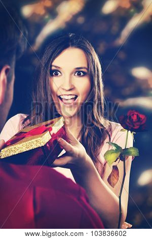 Shocked woman recieving a gift on Valentines Day.