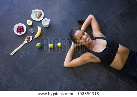 Above shot of a woman lying in the floor with ingredients for an acai bowl or smoothie