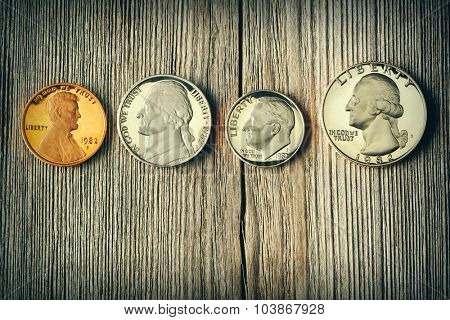 Four US cent coins over wooden background
