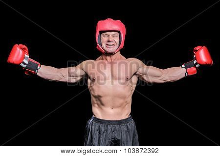 Winner boxer with arms outstretched against black background