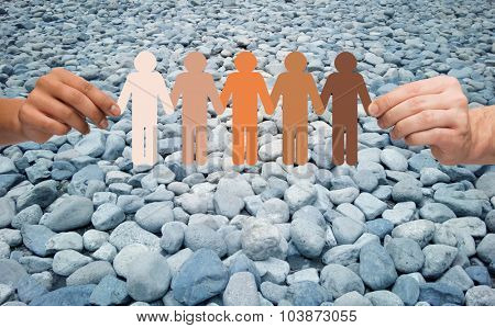 immigration, unity, population, race and humanity concept - multiracial couple hands holding chain of paper people pictogram over stones in desert background