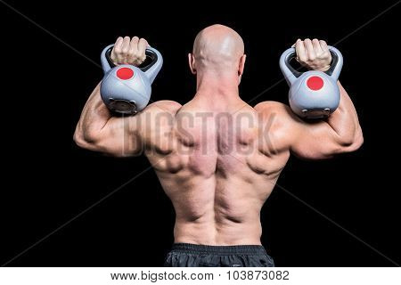 Rear view of bald man lifting kettlebells against black background