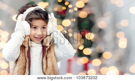 winter, people, childhood and happiness concept - happy little girl wearing earmuffs over christmas tree lights background