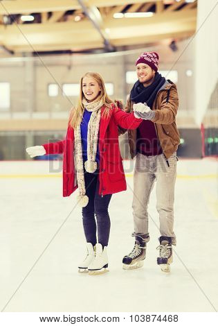 people, friendship, sport and leisure concept - happy couple on skating rink poster