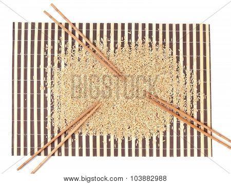 Raw Rice And Chopsticks On Bamboo Carpet