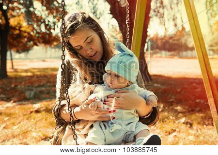 Cute Baby Boy In Mother Sitting Outside The Nature