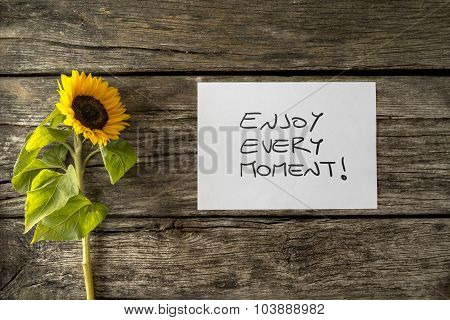 White card with an Enjoy every moment message lying next to a beautiful blooming sunflower on a textured wooden desk in order to encourage you to seize the moment and live a fulfilled life. poster