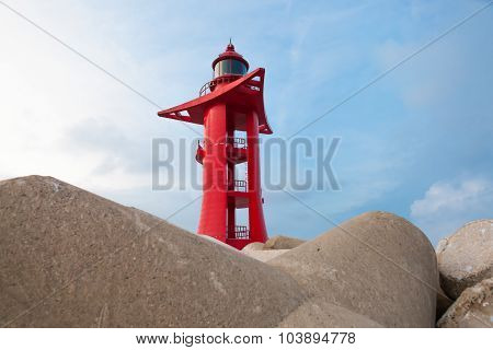 Red Color Lighthouse In Harbor With Sky On Background