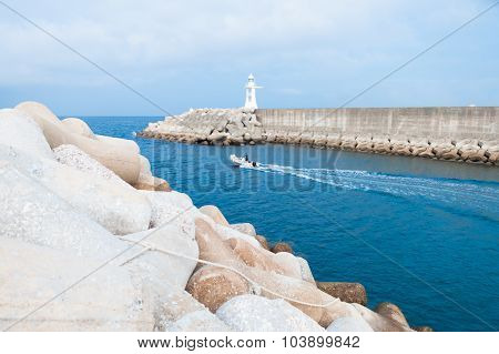 Lighthouse And Boat In Harbor With Sky On Background