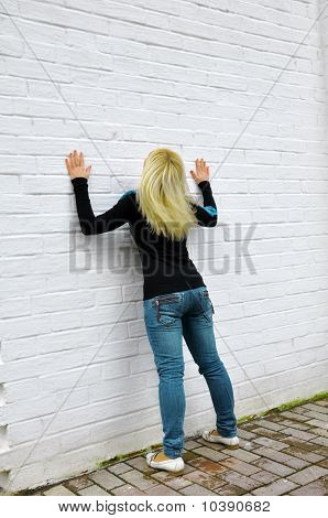 The Girl Costs Near A White Wall