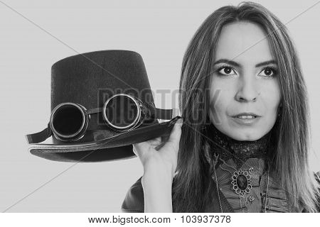 Young steampunk girl holding fancy hat. Fantasy old fashion with topper and goggle. poster