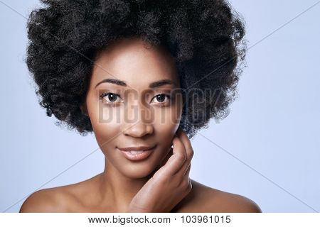 Portrait of beautiful young black african model in studio with smooth complexion flawless skin, skincare beauty concept