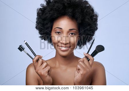 Beautiful black african afro model with flawless complexion and smooth skin holding up different make-up brushes for different applications poster