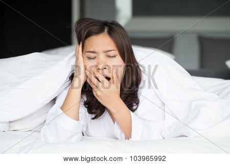 Sleepy Asian Woman Yawning In Bed