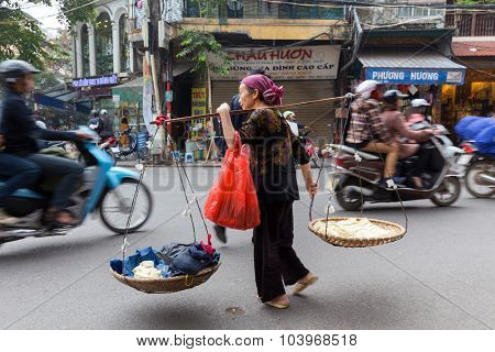 HANOI, VIETNAM, DECEMBER 15, 2014 : A peddler carrying a traditional balance and selling fresh tofu is crossing a busy street in Hanoi, Vietnam