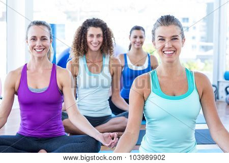 Protrait of women smiling while doing easy pose in fitness studio