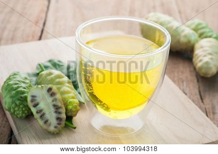 Noni Juice On Glass And Fruit On Cutting Board On Wood Floors.