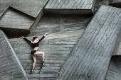Graceful ballerina on the background of the concrete urban structure. Dancer dressed in a black leotard and tights. poster