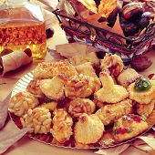 closeup of a plate with panellets, some roasted chestnuts and sweet potatoes in a basket, and sweet wine in a glass bottle, typical snack in All Saints Day in Catalonia, Spain poster