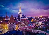 Vintage retro effect filtered hipster style image of Tallinn Medieval Old Town illuminated in evening twilight, with dramatic sky Estonia poster