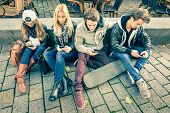 Group of young hipster friends playing with smartphone with mutual disinterest towards each other - Modern situation of technology interaction in alienated lifestyle - Internet wifi connection poster
