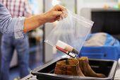 Passenger Puts Liquids Into Bag At Airport Security Check poster