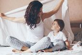 Young mother with her 2 years old little son dressed in pajamas are relaxing and playing in the bed at the weekend together, lazy morning, warm and cozy scene. Pastel colors, selective focus. poster