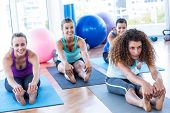 Woman sitting in forward bend pose in fitness studio poster