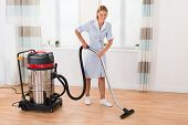 Beautiful Female Maid Cleaning Wooden Floor With Vacuum Cleaner poster