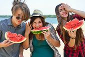 Happy friends eating watermelon on the beach. Youth lifestyle. Happiness, joy, friendship, holiday, beach, summer concept. Group of young people having fun outdoor. poster
