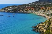 a panoramic view of the Cala de Hort cove in Ibiza Island, Spain, and its traditional fishermen shelters poster