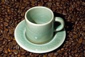 small coffee cup on saucer in bed of beans. demi-tasse. poster