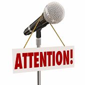 Attention word on a hnaging sign over a microphone urging you to listen or hear an important announcement, news or speech poster