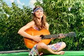 Joyful hippie girl playing the guitar outdoor in the sunny summer day. Child of nature. Lifestyle.   poster