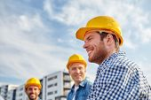 business, building, teamwork and people concept - group of smiling builders in hardhats at construction site poster