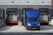 Warehouse loading dock and a blue truck poster