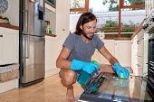 male doing household chores in the kitchen, wiping greasy oven with chemicals poster
