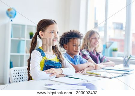 Diligent girl and her classmates listening to teacher explanations by desk