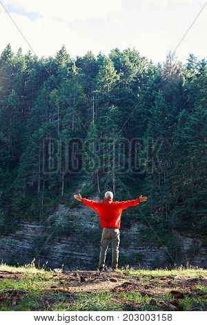 Rear view of hiker outstretched hands while observing cliff view