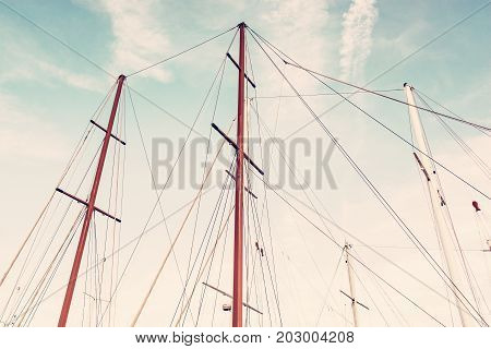 Masts of sailboat and blue sky. Summer vacation. Transport theme. Red photo filter.