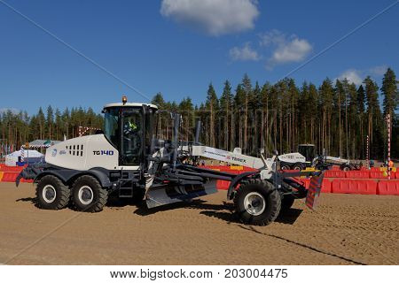 NOVOPRIOZERSK HIGHWAY, LENINGRAD REGION, RUSSIA - SEPTEMBER 11, 2015: Grader competitions during the final of Russian professional skills championship of road workers