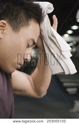 Chinese man wiping head with towel