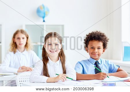 Three intercultural youngsters with pencils sitting by desks