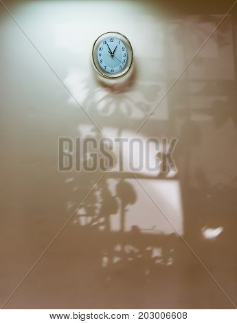 Round metal clock  the rays on a light wall with a dark shadow from the window and flowers