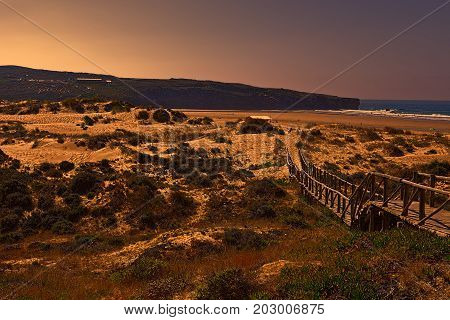 Wooden Footbridge across the Sand Dunes on the Atlantic coast of Portugal at Sunset